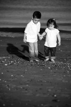 little boy and girl: Brother and sister walking hand in hand at the beach Stock Photo
