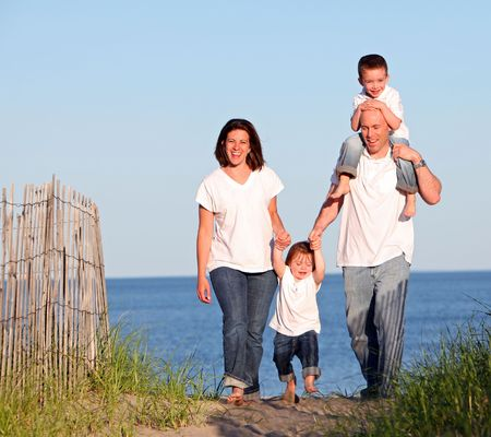bald girl: Good looking family going for a walk at the beach at sunset