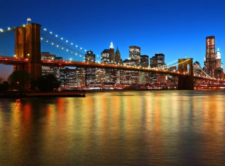Historic Brooklyn Bridge and lower Manhattan reflected in East River