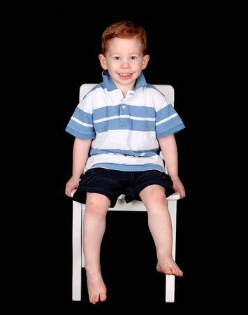 Leuke roodharige jongen zittend op een witte stoel