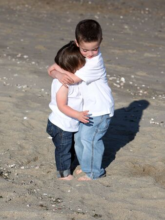 Young brother and sister embracing on a sandy beach 版權商用圖片