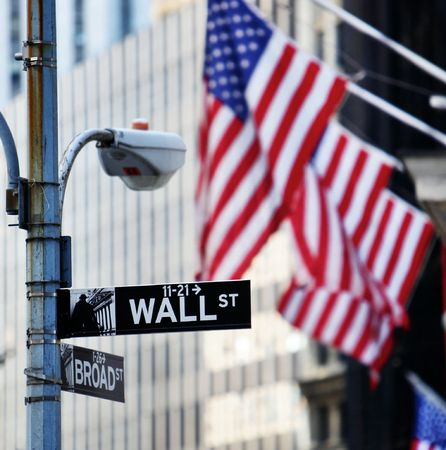 main market: Wall street sign in New York with New York Stock Exchange background