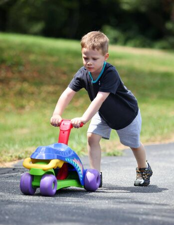 Young boy pushing a toy bike uphill 스톡 콘텐츠