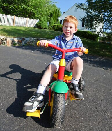 Happy young boy playing outside on a bike photo