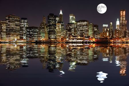 Lower Manhattan in New York City at night with reflection in water photo
