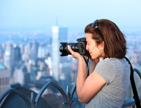 Attractive female photographer at sunset on top of a skyscraper Stock Photo