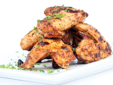 Cooked chicken wings in a sauce on a white plate