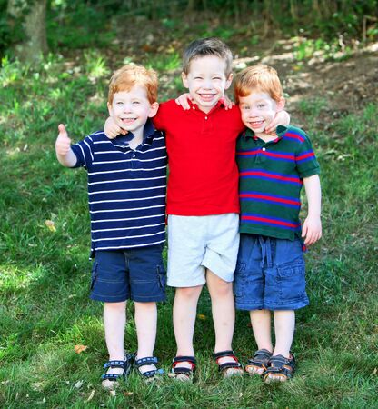 Three cute brothers standing outside on grass portrait photo