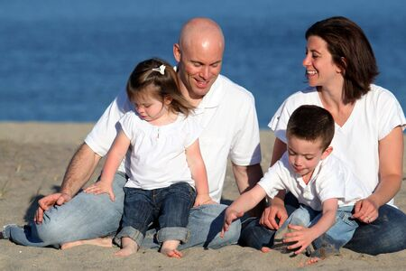 Happy family portrait relaxing at the beach photo