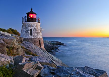 newport: Beautiful lighthouse by the ocean at sunset Stock Photo