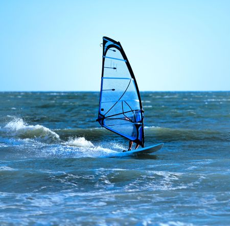 watersport: Lone anonymous windsurfer in the ocean catching a wave