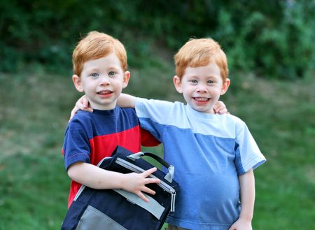Twin boys with arms around eachother outside portrait