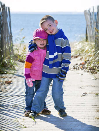 Brother and sister at the beach in winter photo