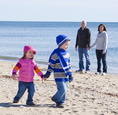 Handsome family walking at the beach with focus on little girl photo