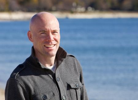 행복 한 잘 생긴 남자가 웃는 세로 해변에서
