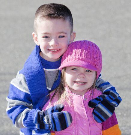 かわいい弟と妹冬抱き締める外の