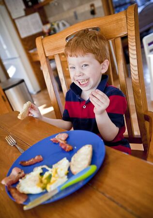 mealtime: Happy redhead boy eating bacon and eggs at a table