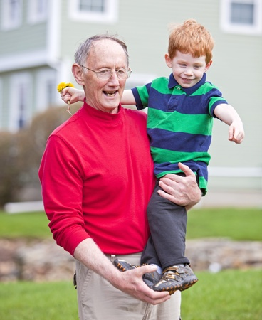 grandad: Grandfather carrying redheaded grandson outside on grass Stock Photo