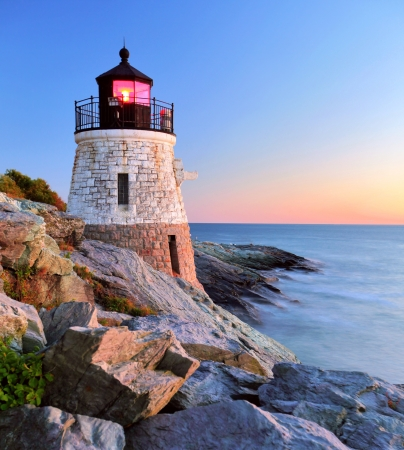Beautiful old lighthouse on rocks at sunset  Stock Photo