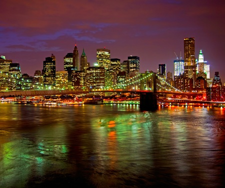 Historic Brooklyn Bridge and lower Manhattan reflected in East River  Stock Photo