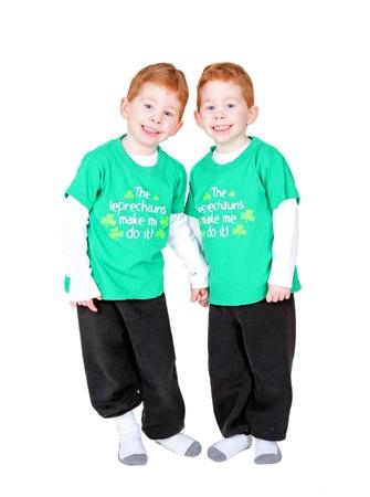 Souriant jumeaux attirante, main dans la main, isolé sur fond blanc