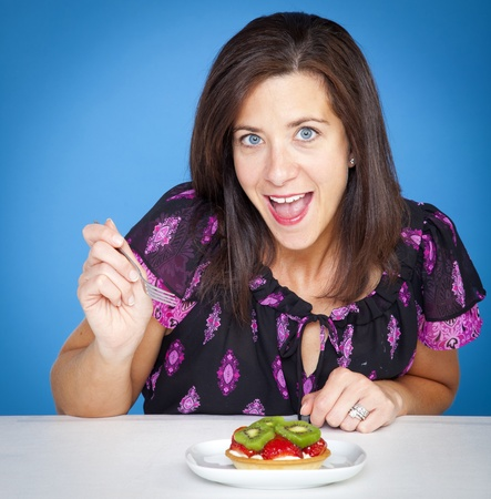 Atractive woman with a fruit tart in studio photo
