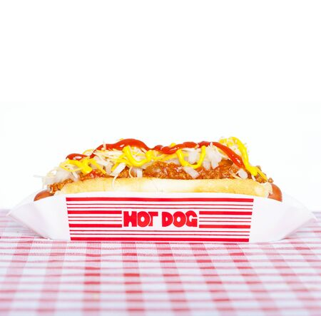 Hot dog with chili, raw onion and sauces on a tablecloth photo