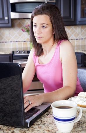 trabajando en casa: Mujer en rosa trabajo superior en su equipo port�til Foto de archivo