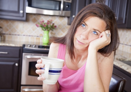 Bored woman sitting in kitchen drinking a cup of coffee