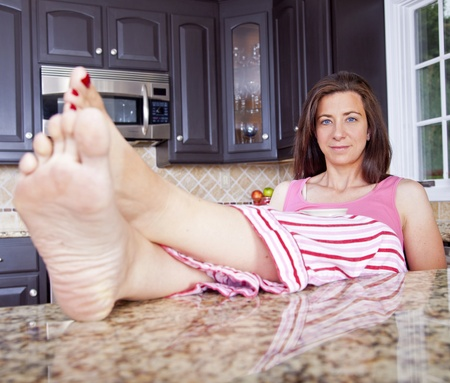 pjs: Attractive woman sitting in kitchen with feet on counter