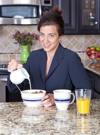 Attractive businesswoman pouring milk over her cereal photo