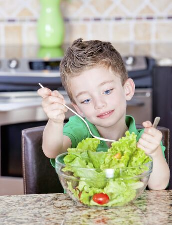 one child only: Young boy in kitchen mixing a salad in a bowl