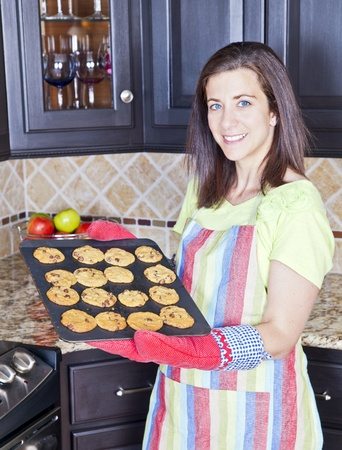 housewife gloves: Pretty woman with a tray of freshly baked cookies Stock Photo