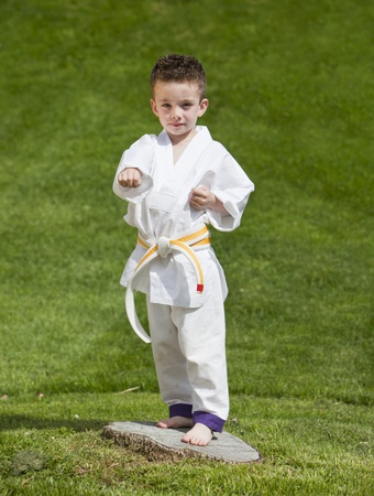 Young boy practicing martial arts outside in spring photo