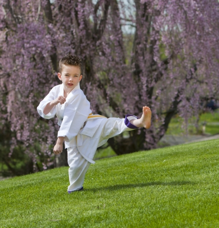 Young boy practicing martial arts outside in spring Banco de Imagens