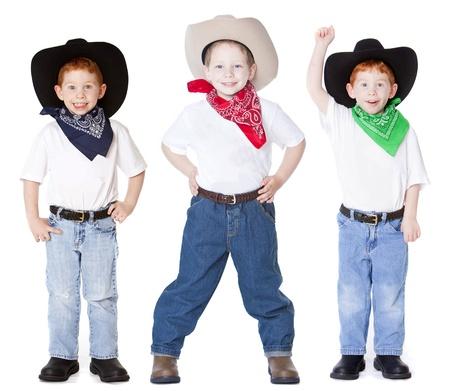 Three boys dressed up as cowboys in studio