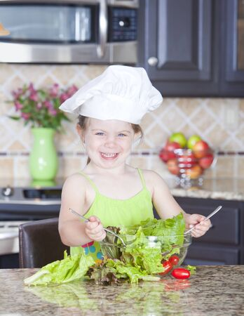 side salad: Cute little girl playing with a bowl of salad