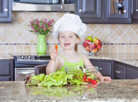 Cute little girl playing with a bowl of salad photo