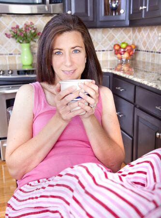 striped pajamas: Atractiva mujer sentada en la cocina con los pies sobre la lucha contra