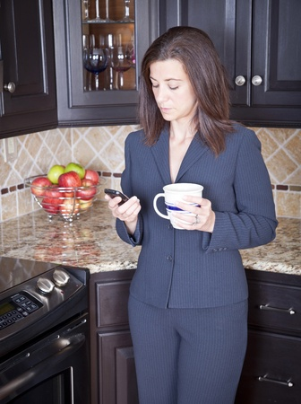 Young businesswoman checking her cell phone in kitchen photo