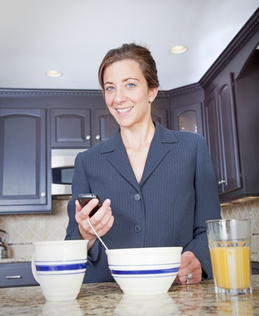 Bussinesswoman holding a cell phone having breakfast at home photo