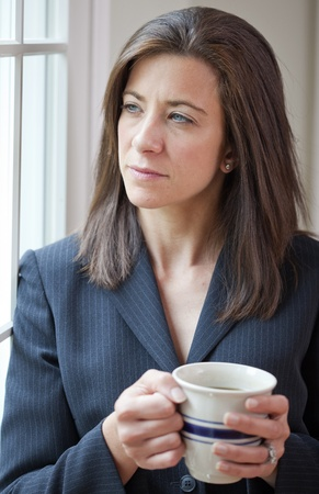 Professional businesswoman holding coffee cup looking thoughtful