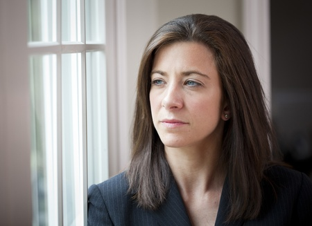 concerned: Attractive young woman in suit looking out of window