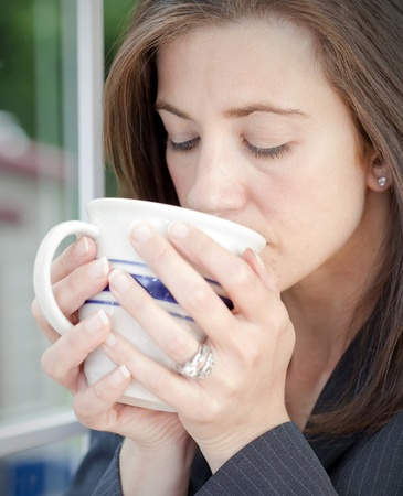 Young businesswoman sipping from a coffee mug photo