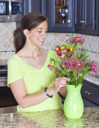 Pretty woman arrabnging a bunch of flowers in a vase photo