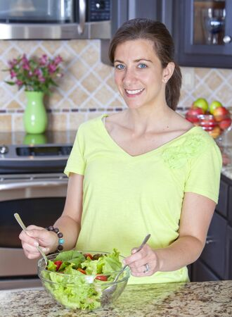 Pretty woman mixing salad in a glass bowl photo