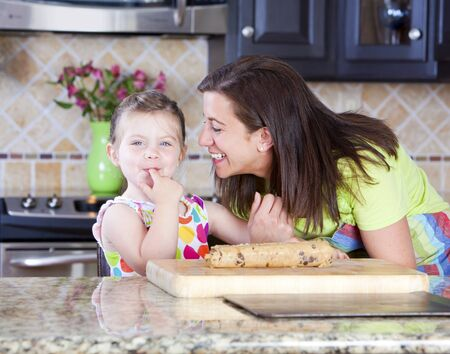 Mother and daughter putting cookie dough onto baking sheet in kitchen  Stock Photo - 11560592