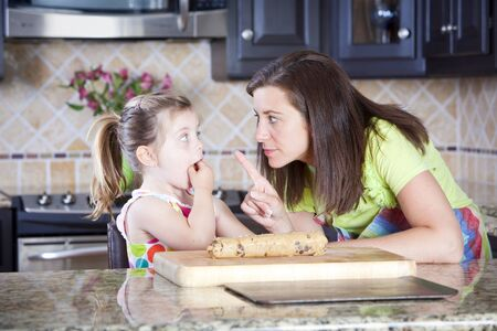 Mother and daughter putting cookie dough onto baking sheet in kitchen  写真素材