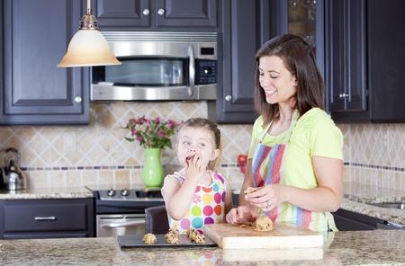 madre trabajando: Madre e hija poniendo la masa de galletas sobre una bandeja para hornear en la cocina