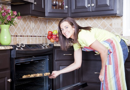 stove: Pretty woman opening oven with a tray of cookies